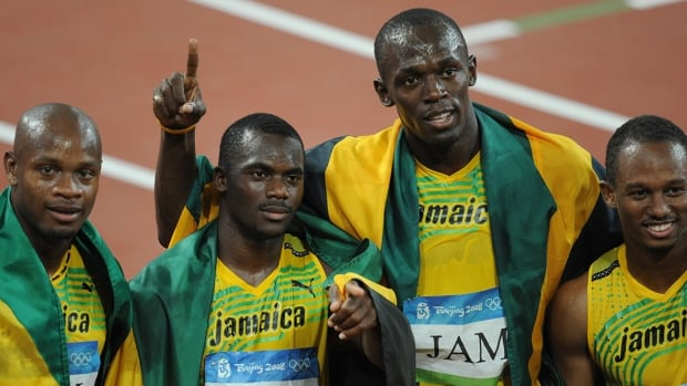 Sprinter Nesta Carter, second from left, who ran the opening leg on the 2008 Jamaican Olympic relay team anchored by Usain Bolt, second from right, joined the mounting list of athletes who have retroactively tested positive for a banned substance.