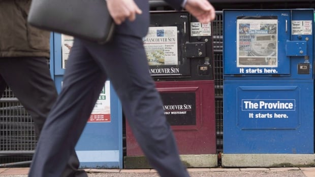 A man walks past newspaper boxes containing the Vancouver Sun and the Province in downtown Vancouver.