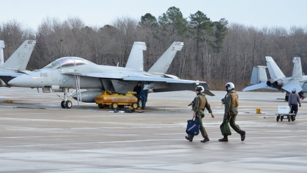 A U.S. navy air crew walks the flight line in front of a squadron of Super Hornet fighters at Naval Air Station Oceana in Virginia last week. Canada has opened negotiations for the sole-source purchase of 18 of the advanced jet fighters.