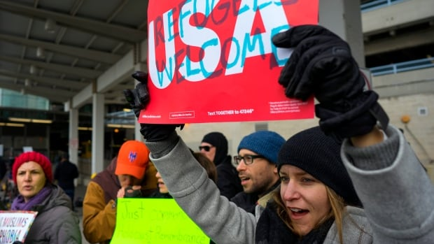 Protesters assemble at John F. Kennedy International Airport in New York City on Saturday after two Iraqi refugees were detained while trying to enter the country.
