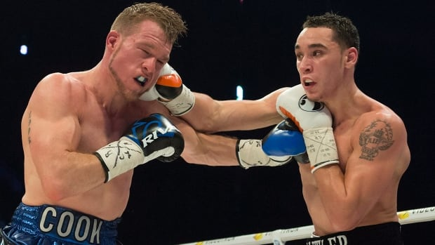 Steven Butler, right, and Brandon Cook trade punches during boxing match in Montreal on Saturday. A brawl broke out in the crowd following the match.