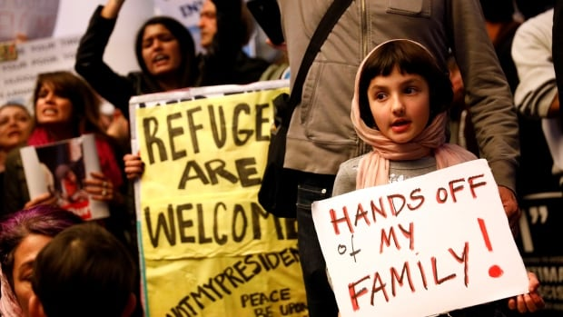 A child holds a sign in support of Muslim family members as people protest against U.S. President Donald Trump's travel ban on Muslim majority countries at the international terminal at Los Angeles International Airport.