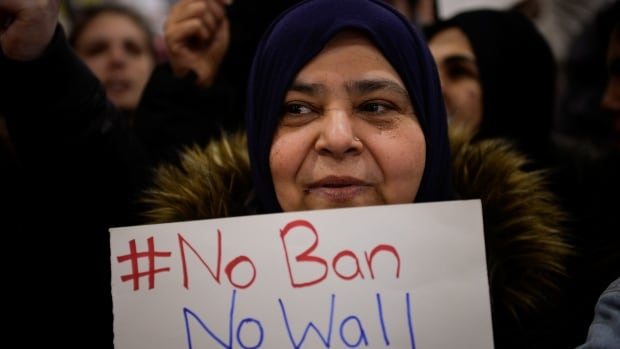 A Muslim women holds a sign during protests outside Philadelphia International Airport.
