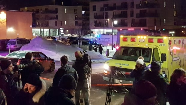 An ambulance is parked at the scene of a fatal shooting at the Quebec Islamic Cultural Centre in Quebec City. Police say multiple people were killed.