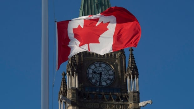 The flag flies at half-mast on a flag pole near the Peace tower on Parliament Hill Monday in memory of the victims of the Quebec City shooting.
