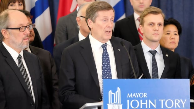Mayor John Tory introduced a new motion Tuesday affirming the city's status as a sanctuary city. Councillors Joe Mihevc, left, and Joe Cressy, right, seconded the motion, which was overwhelmingly approved by council.