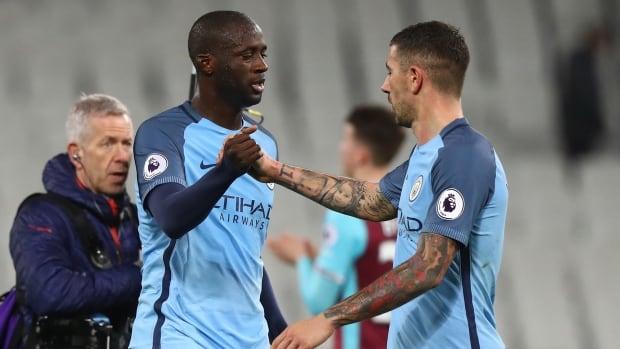 Yaya Toure of Manchester City celebrates with Aleksandar Kolorov of Manchester City after beating West Ham United 4-0 on Wednesday.