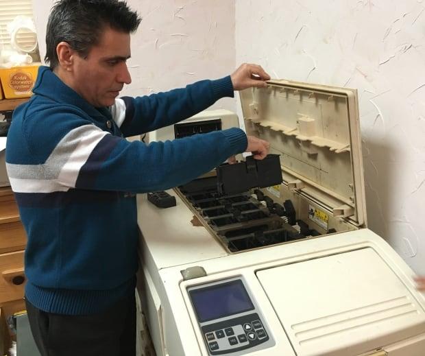 Keyvan Ashenaei shows off old film developing machine
