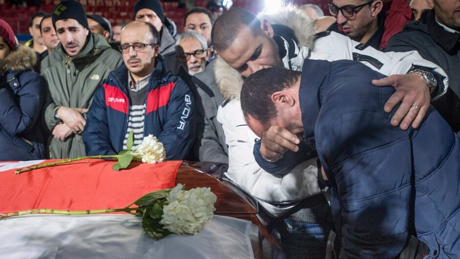A man breaks down next to the caskets of three of the six victims of the Quebec City mosque shooting during funeral services at the Maurice Richard Arena Thursday, February 2, 2017 in Montreal.