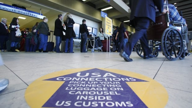 Passengers wait to check in and go through U.S. Customs at Calgary International Airport. U.S. border guards working at pre-clearance stations would be given expanded powers under a proposed Liberal law.