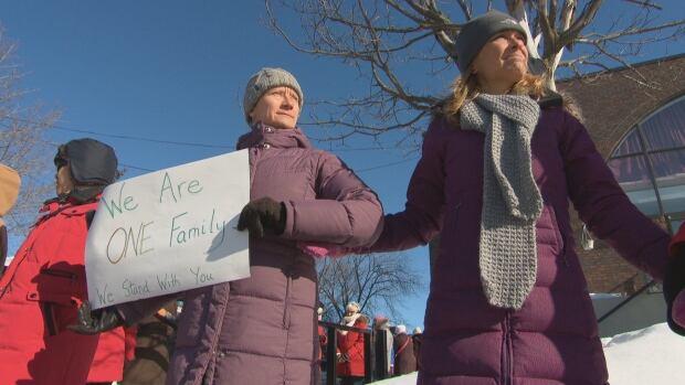 Andrea Prazmowski, left, joins the human chain at the Ottawa Mosque Feb. 3