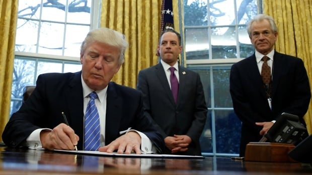 U.S. President Donald Trump with White House chief of staff Reince Priebus and trade adviser Peter Navarro. Navarro suggested Germany was manipulating the value of the euro to obtain a trade advantage.