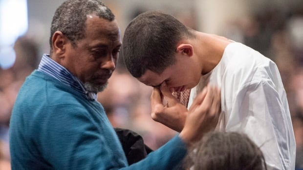 Ilies Soufiane, 15-year-old son of Azzeddine Soufiane, one of six people killed in last week's attack on a Quebec City mosque, is consoled during the funeral for three of the victims.