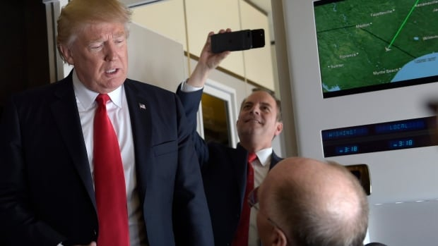 White House chief of staff Reince Priebus takes a picture as U.S. President Donald Trump speaks to reporters on Air Force One while travelling to  West Palm Beach, Fla., on Friday. While Trump spends the weekend at Mar-a-Lago, some members of his Republican Party are expressing dissent about his policies.