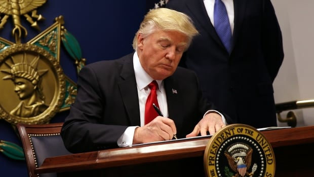U.S. President Donald Trump signs his controversial executive order to impose tighter vetting of travellers entering the U.S.