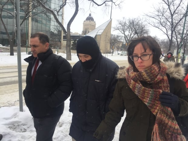 VInce Li, now known as Will Baker (centre), walks out Winnipeg's Law Courts Monday with his hood pul