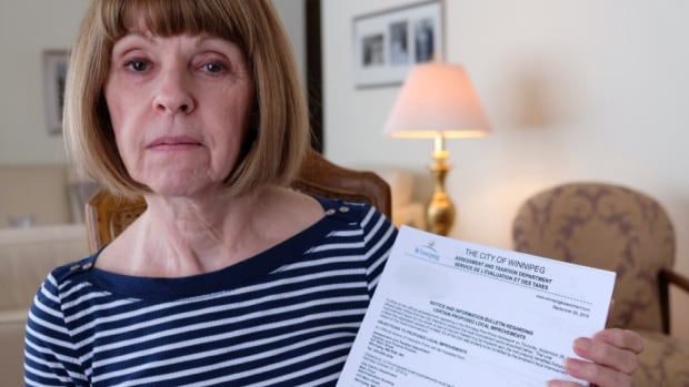 Cherry Karpyshin holds the notice she received from the city that outlines $76,000 in proposed fees on her and her husband's property.