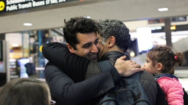 Iranian citizen and U.S green card holder Cyrus Khosravi, left, greets his brother, Hamidreza Khosravi, centre, and niece, Dena Khosravi, right, 2, after they were detained for additional screening following their arrival at Seattle-Tacoma International Airport, during a pause in U.S. President Donald Trump's travel ban.