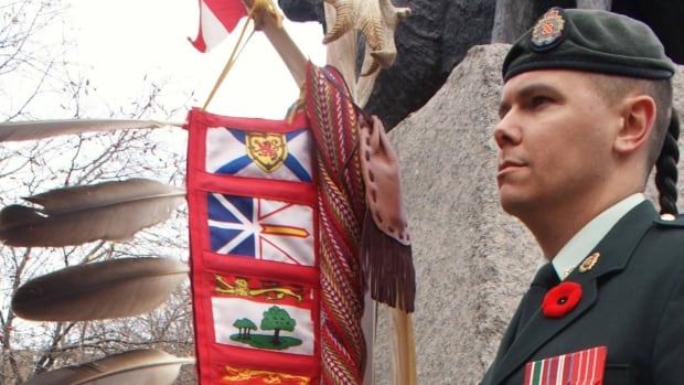 Sgt. Moogly Tetrault-Hamel, the first Indigenous adviser to the Chaplain General, holds the Canadian Armed Forces Eagle Staff, at the National Aboriginal Veterans Monument during Remembrance Day 2016.