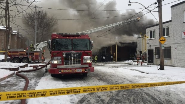 Smoke billows from an industrial building in the west end as crews work to contain a fire.