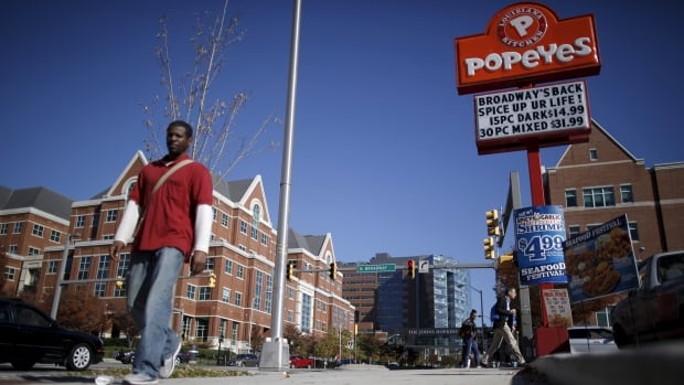A man walks by a Popeyes Louisiana Kitchen restaurant in Baltimore, Md., in this Nov. 2015 photo. Reuters says Oakville, Ont.-based Restaurant Brands has approached Popeyes about a takeover.