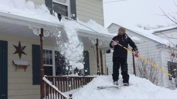 A Moncton man is shown clearing snow off his porch roof after a storm last February. Two children were recently buried in snow that fell from a roof in Woodstock, N.B. They were not injured.