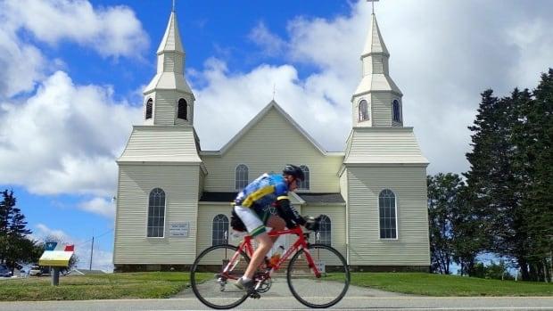 A cyclist in the Gran Fondo Baie Sainte-Marie pedals past Église Saint-Alphonse Church.