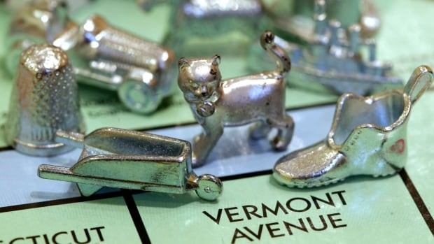 The thimble game piece, left, sits among other Monopoly tokens at Hasbro Inc., headquarters in Pawtucket, R.I., in this Feb. 2013 photo. The thimble will no longer be a piece in Monopoly, rejected in 2017 in a campaign to determine the tokens for the next generation of the game.