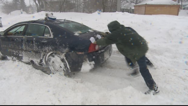 Two people push a car stuck in snow on a Moncton street on Thursday.