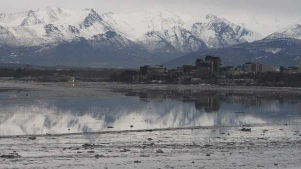 A file photo shows downtown Anchorage Alaska reflected in the still waters of Cook Inlet. Natural gas is bubbling from a 20-centimetre pipeline in 24 metres of water about six kilometres off shore.