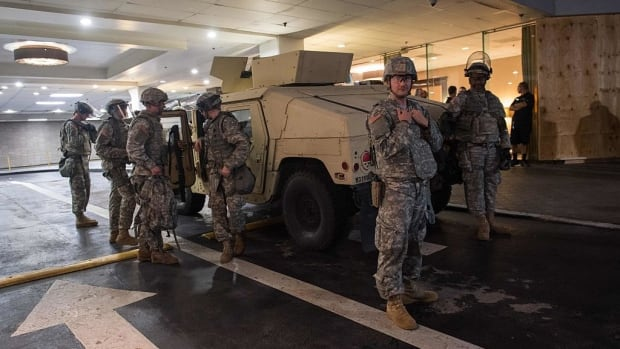 Members of the National Guard stand outside the entrance of a hotel in Charlotte, N.C., on Sept. 22, 2016. A report says the Trump administration is considering a proposal to mobilize as many as 100,000 National Guard troops to round up unauthorized immigrants. The White House has denied that.