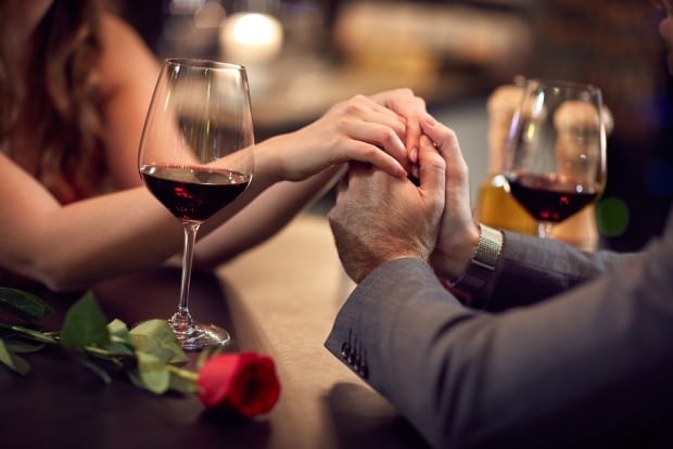 Couple holding hands with red wine and red rose