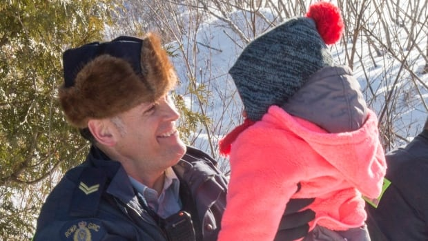 Family members are helped into Canada by RCMP officers along the U.S.-Canada border near Hemmingford on Friday.