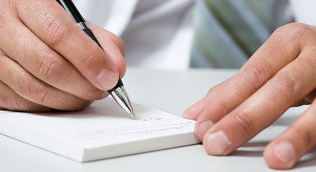 Shutterstock prescription pad doctor signing