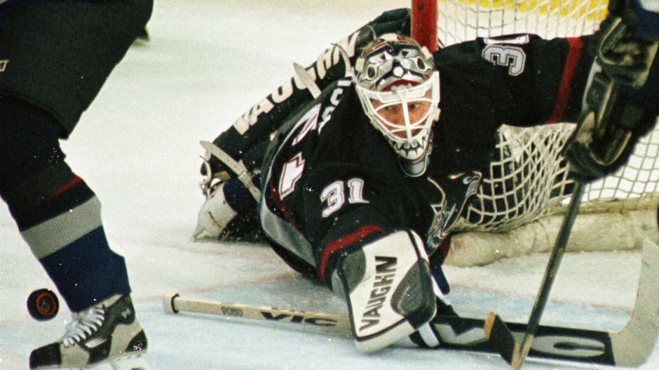 Vancouver Canucks goalie Corey Hirsch (31) blocks a shot by Pittsburgh Penguins' Robert Lang during the first period in Pittsburgh on Feb. 11, 1999.