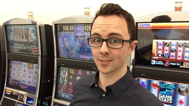 Lead author Spencer Murch in front of the bank of slot machines at UBC's Centre for Gambling Research.
