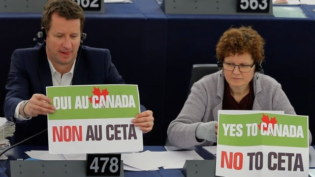 "French politician Yannick Jadot (left , green party EELV (Europe-Ecologie-les-Verts) candidate for the 2017 French presidential election and Member of the European Parliament sits behind a placard that reads ""Yes to Canada, No to CETA"" as he waits for the start of a voting session on CETA.  The deal passed, but French politicians are now challenging it in court."