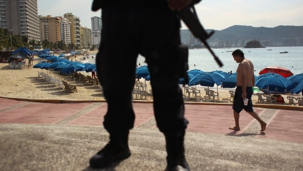 A federal police officer stands guard near a beach in Acapulco. The beach town's murder rate per capita has earned it the title of Mexico's most dangerous city.
