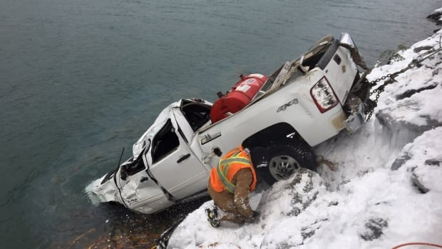 A team works to recover the truck that Ryan Bremner was in, when he slid down a 45-metre embankment into a freezing cold lake.