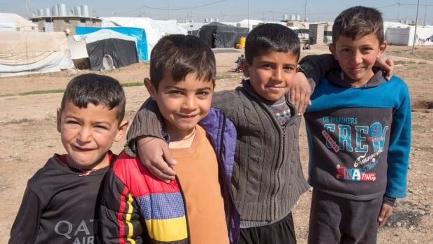 A group of Yazidi boys pose for a photo at a camp for internal displaced persons, Wednesday, in Dohuk, Iraq.