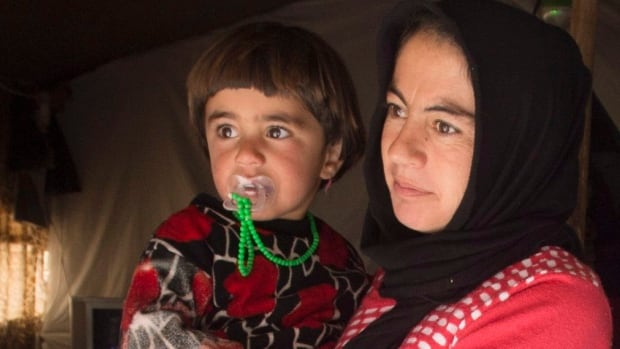 A Yazidi woman and her child stand at the door of their tent at a camp for internal displaced persons Wednesday, Feb. 22, 2017 in Dohuk, Iraq. Canada has promised to accept hundreds of Yazidi refugees by the end of this year.