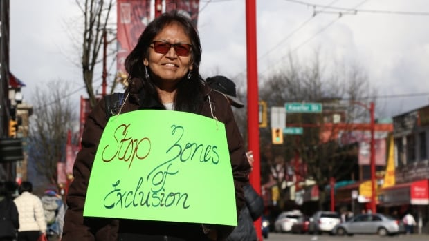 Erica Grant uses a sign to show her opposition to gentrification in Vancouver's Downtown Eastside.