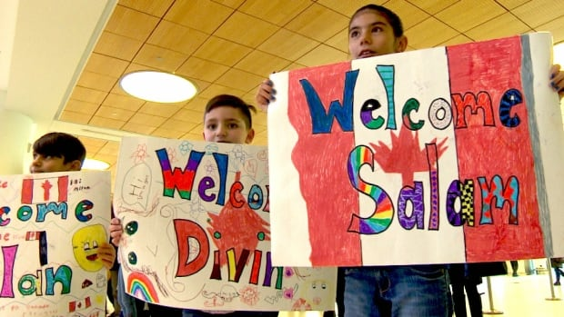 A group of children held signs welcoming a Yazidi refugee family to the airport in Winnipeg on Wednesday.