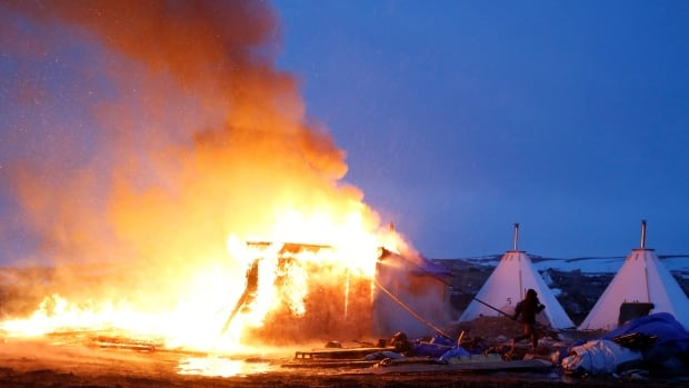 A building burns after it was set alight by protesters preparing to leave the main opposition camp against the Dakota Access oil pipeline near Cannon Ball, N.D., on Wednesday.