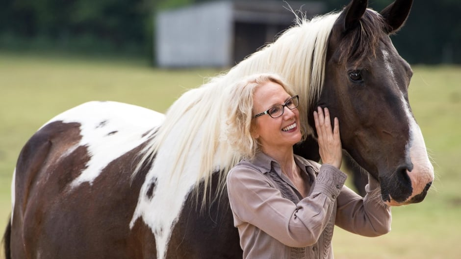 Laurie Wheeler poses with her horse Jazz. Wheeler is fighting the state of Tennessee, which has barred her from practising massage therapy on horses without a veterinary licence.