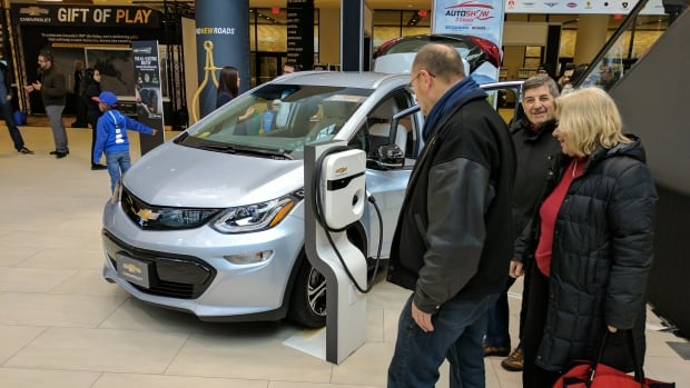 People check out a Chevy Bolt at the 2017 Toronto International Auto Show