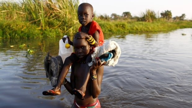 Children cross a body of water to register for a UN food distribution program in Thonyor, South Sudan, Saturday.