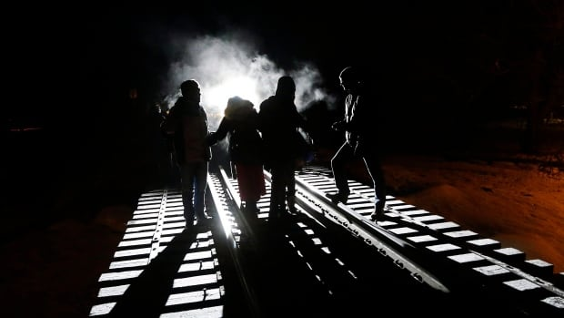 Asylum seekers move carefully along a railway overpass in Emerson, Man. Many of the people coming into Manitoba are originally from Somalia.