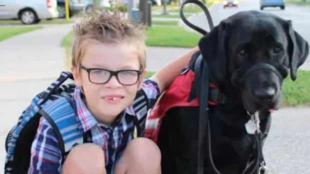 Grade 3 student Kenner with his autism service dog Ivy.