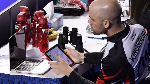 Adam Kingsbury works with a laptop and iPad as the Rachel Homan rink takes on Alberta during the Scotties Tournament of Hearts in St. Catharines, Ont., on Monday, Feb. 20, 2017.